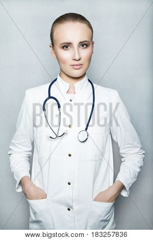 Close up portrait of a young female doctor with nude make up in white gown and with stethoscope on her neck holding her hands in pockets on white background