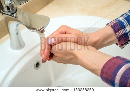 Close-up of hands washing under water jet coming out of tap