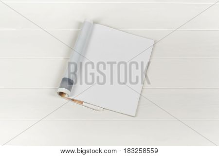 Mock-up magazine or catalog on white wooden table. Blank page or notepad on wood background. Blank page or notepad for mockups or simulations.