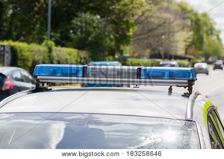Light bars on unidentified British police vehicle monitoring traffic on a busy main road or highway with defocussed traffic in the background