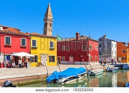 BURANO, ITALY - APRIL 20, 2016: Old colorful houses along canal with motorboats in Burano - island in Venetian lagoon, popular tourist destination, known for its lace work and brightly colored homes.