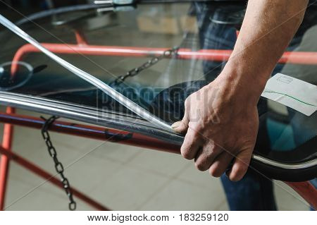 Car mechanic's hands are instilling decorative molding to seal of a windshield.