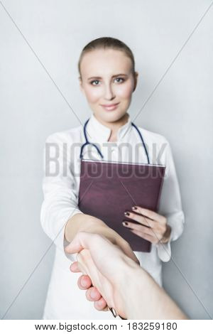 Portrait of a young female smiling doctor in white gown and with stethoscope holding medical brown journal in her hand and shaking hand of a patient or physician on white background.