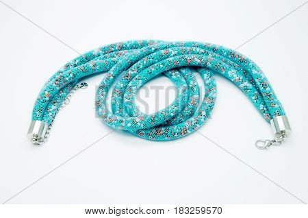 on a white background lies a necklace on the neck with a blue gem as a gift to a beloved woman