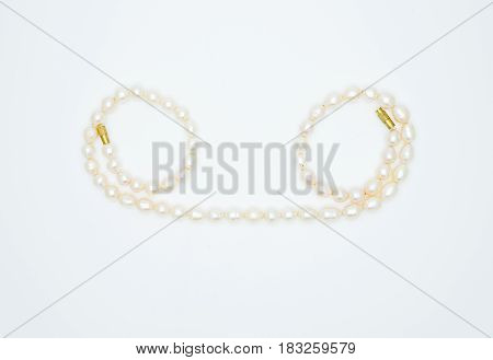on a white background lies a pearl necklace on the neck precious as a gift beloved woman