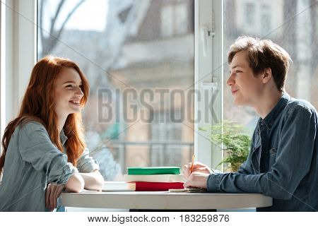 Two young smiling students talking in cafe