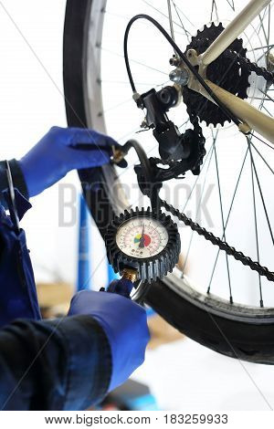 Pumping the bike. The mechanic in the bike service pumped the bike wheel with a compressed air compressor.