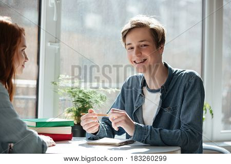 Smiling male student with pencil looking camera while sitting in cafe
