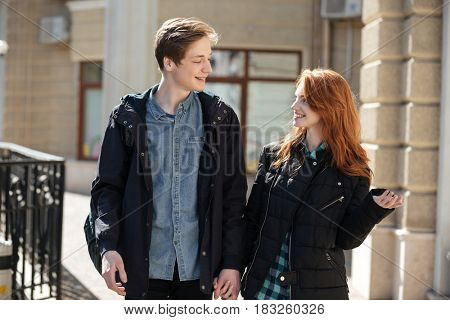 Cute couple, yound man and redhead oman, walking after lessons