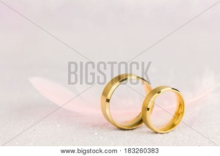 Two Golden Wedding Rings and Light Angelic Feather - gentle soft background for marriage, vintage toned