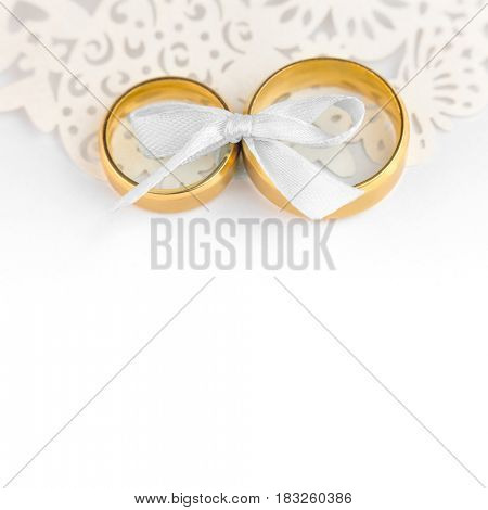 White Wedding Celebration background - pair of wedding rings with bow and copy space for text