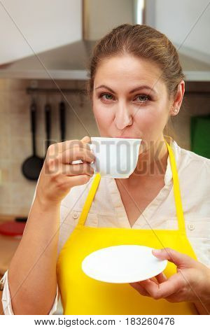 Mature woman in apron drinking cup of coffee in kitchen. Housewife female with hot energizing beverage. Caffeine energy.