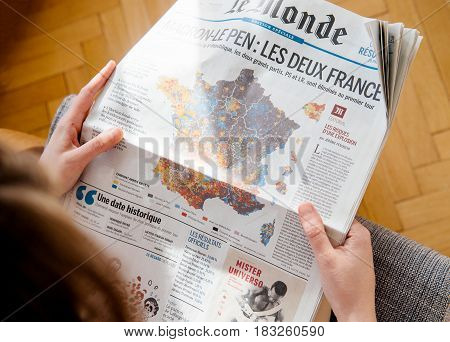 PARIS FRANCE - APR 24 2017: POV above French map electins result on newspaper cover - woman reading the French newspaper Le Monde a day after the first round of the French Presidential election on April 24 2017