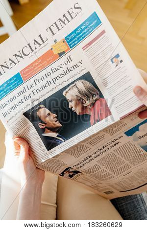 PARIS FRANCE - APR 24 2017: POV personal perspective on Financial Times newspaper cover - woman reading the French newspaper a day after the first round of the French Presidential election on April 24 2017
