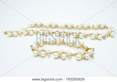 on a white background lies a pearl necklace on the neck and bracelet precious as a gift beloved woman