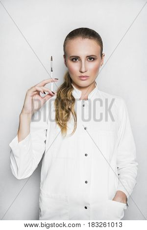 Beautiful blonde female doctor or scientist with nude make up in white medical gown holds a syringe in hand on white background. She is ready to give an injection