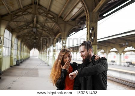 Girl come late on the railway station. Unhappy man show on the watch and look on girlfriend face. Delay concept. Miss the train.