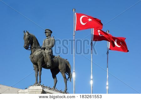 The national flags of modern Turkey and statue of Ataturk - Ankara, Turkey