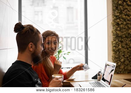 Online shopping concept. Wife bought expensive dress in the internet and spent all money. Stressed husband look on his woman with upset and disappointed face. Copy space for advertising text.
