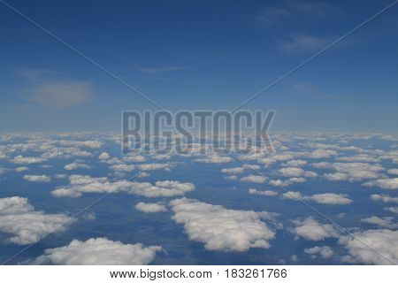 Traveling by air. View through an airplane window. Cirrus and cumulus clouds and little turbulence, showing Earth's atmosphere