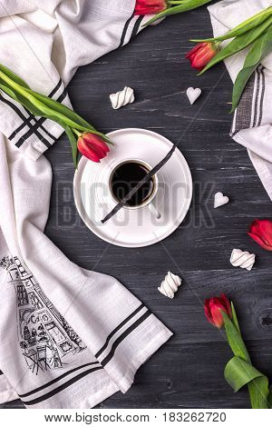 Black coffee in a white cup, vanilla bean, marshmallow and red tulips on a dark wooden background. Top view
