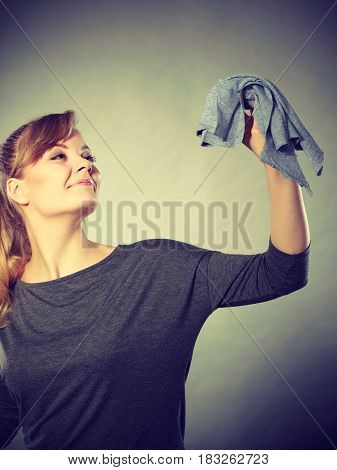 Household duties concept. Young energy girl playing with cleaning cloth doing domestic chores. Cheerful playful housewife ready to clean house.