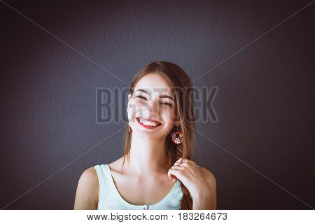 Young smiling woman standing near dark wall .