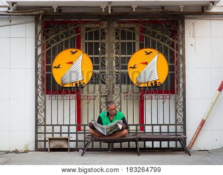 Semarang, Indonesia - september 13, 2015: Traditional street scene with man reading a newspaper in Semarang, Indonesia