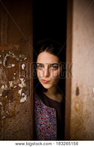 A Young Curious Girl Looks Out From Behind The Door Of Her House. She Thinks About Going Outside. Ag