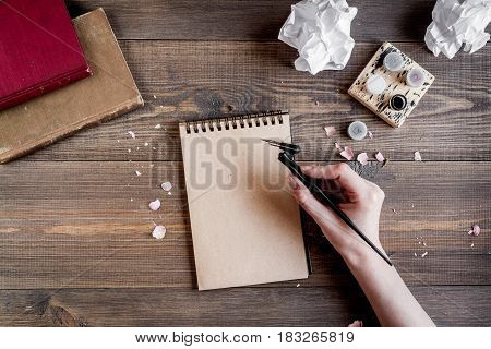 Writer workplace with tools, copybook and hands on wooden table background top view