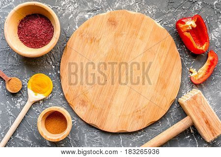 Professional cook workplace with kitchen tools and sweet pepper and spices on gray table background top view