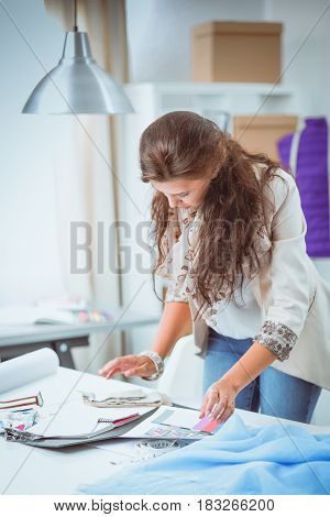 Smiling female fashion designer sitting at office desk .