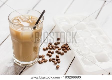 coffee break with cold iced latte and beans in caffee on white table background