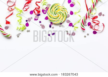 birthday party set with colorful confetti and sweets on white desk background top view mock up