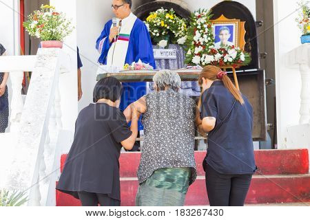 CHIANG RAI THAILAND - APRIL 19 : unidentified asian old woman with her helpers waking up the steps at thai traditional Christian funeral on April 19 2017 in Chiang rai Thailand.