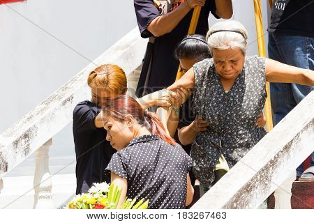 CHIANG RAI THAILAND - APRIL 19 : unidentified asian old woman walking down the steps in thai traditional Christian funeral on April 19 2017 in Chiang rai Thailand.