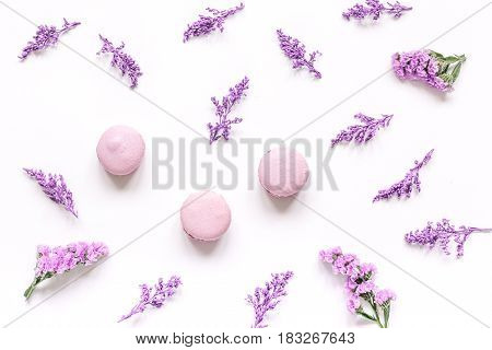 spring woman breakfast with macaroons and mauve flowers white background top view pattern