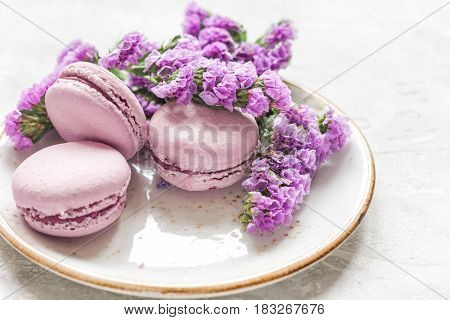Trendy woman pattern with spring flowers and macaroons on plate white background