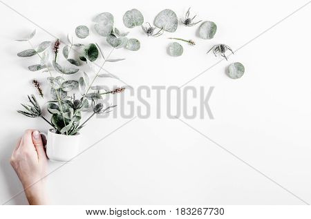 Modern spring design with green plants and hand on white desk background top view mock-up