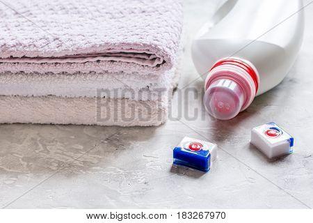 Plastic bottle of detergent with pastel towel pile on light desk background