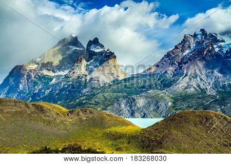 National Park Torres del Paine. Strong wind drives the heavy gray clouds above the cliffs of Los Kuernos. The concept of active and adventure tourism. Travel in Chile