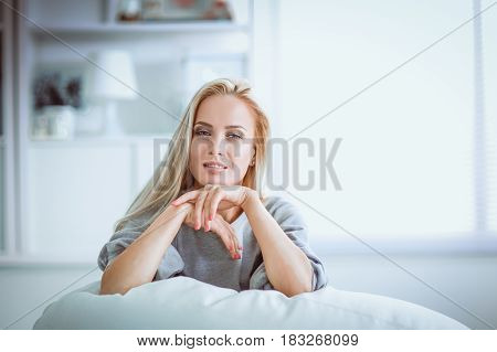 Woman sitting on a sofa in her house with camera.