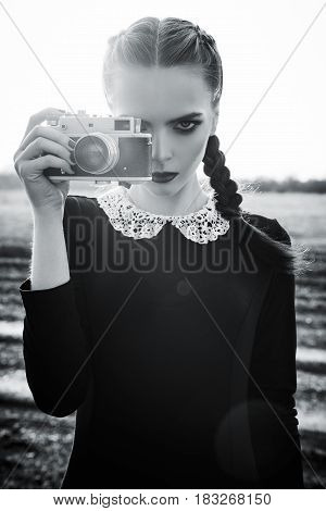 Beautiful sad young girl photographing on the vintage film camera. Black and white