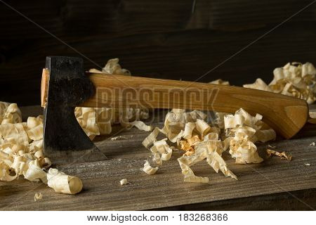 Woodworking carving axe tool on wooden boards in carpenter's workshop against dark brown background with copy space