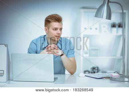 Young businessman working in office, sitting at desk .