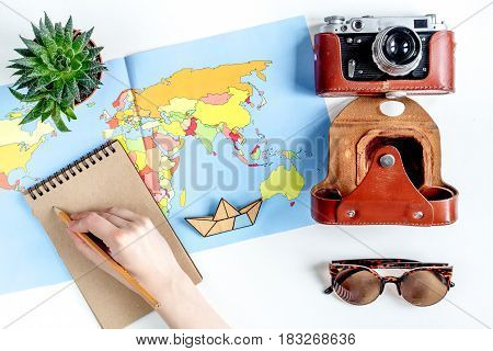 vacation concept with traveller outfit map and camera on white desk background top view