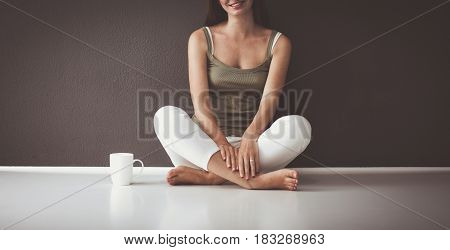Attractive caucasian girl sitting on floor with cup and tablet near wall.