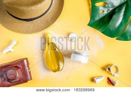 Sun protection cosmetic cream and lotion with beach outfit, camera and hat on orange background top view