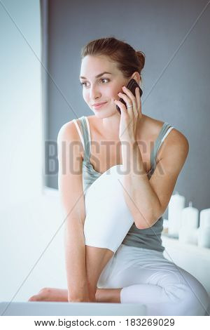 Attractive caucasian girl sitting on floor with phone.