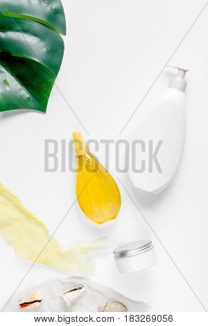 Sun protection concept with cream, lotion set and plant on white background top view